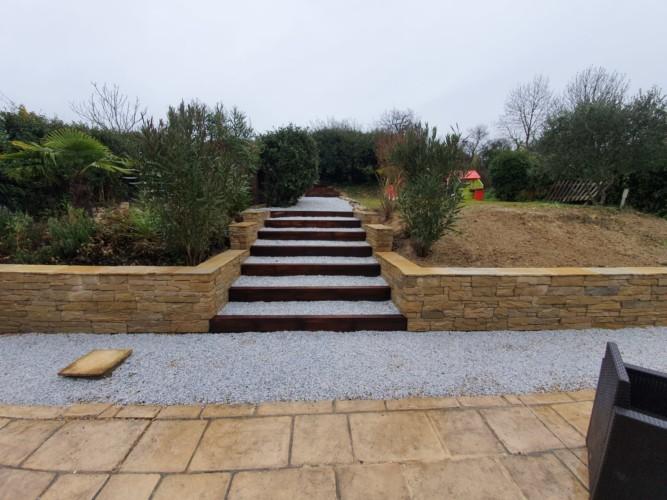 Mur de soutènement, parement en pierre naturelle, escaliers en bois réalisés par Les Jardins d'Oc